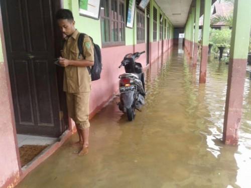 Di Guyur Hujan, Puluhan Siswa Laksanakan UN di Atas Banjir